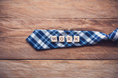Necktie and the message work put on wooden floor - Concept of lifestyle for businessman.