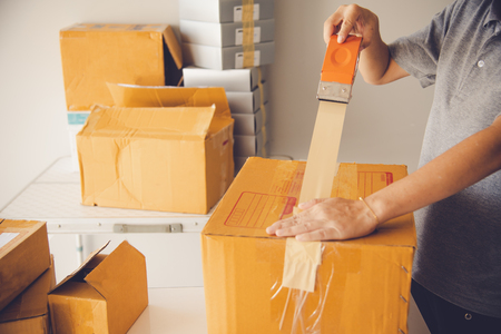 Hand holding closed-up tapes to pack products to prepare shipments.