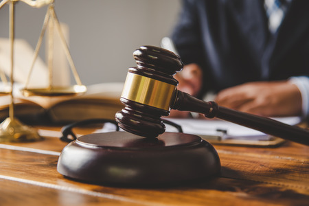 Law theme, mallet of the judge, law enforcement officers, evidence-based cases, and documents taken into account. Stock Photo