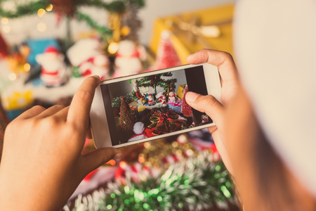 Girl hands holding Christmas tree beautifully decorated phone. Banco de Imagens