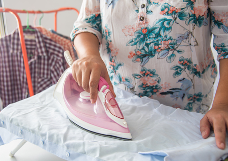 Close up of woman ironing clothes on ironing board