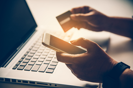 Hand holding a credit card in their hands and find information about a product using their mobile device to make purchases online and conduct financial transactions.