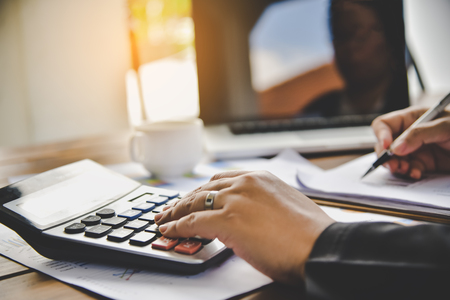 Businessman are working with a calculator and document. Meeting report in progress. in office business concept Banco de Imagens