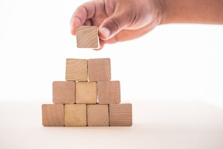 The hand of the businessman caught the wooden blocks placed on a white background as a house to show the stability of doing business.