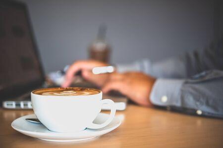 Kubek do kawy postawiony na biurku