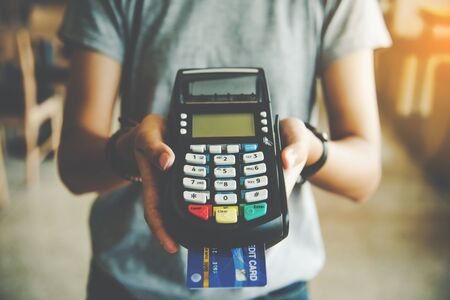 Close up of hand hold credit card swiping machine to pay. Online payment . Paying by credit card Reklamní fotografie