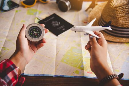 Tourists hold a compass and locate a place on a world map. Reklamní fotografie