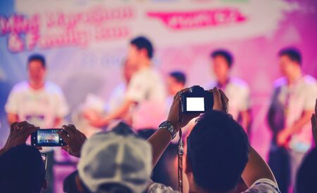 Fans are having fun, both taking pictures with the camera and mobile phone. Concert performer