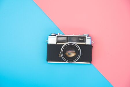 Old film camera placed in the color background