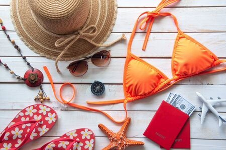 Beauty orange bikini and accessories on wooden floor for trip on summer Reklamní fotografie