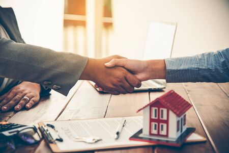 Real estate agents and Clients join hands to congratulate them on achieving contractual agreements, regarding insurance, done business deal for transfer right of property.