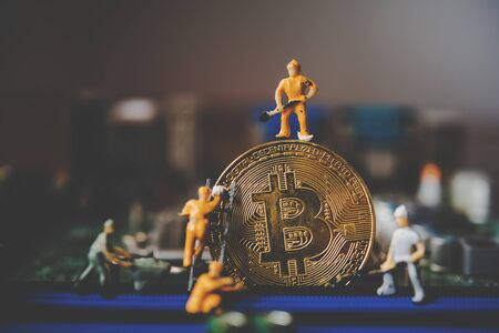 Miniature people or small figure worker on  gold bitcoin.  Bit coin cryptocurrency banking money digital Bit Coin BTC Currency Technology Business Internet Concept. Фото со стока