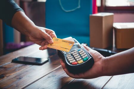 Close up of hand using credit card to pay by sending the credit card to the staff at the credit card swipe machine. Online payment Фото со стока