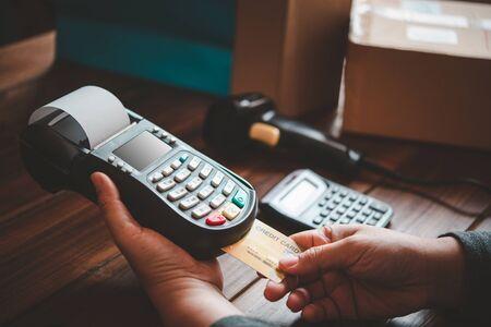 Paying by credit card , buying and selling products using a credit card swipe machine Stock Photo