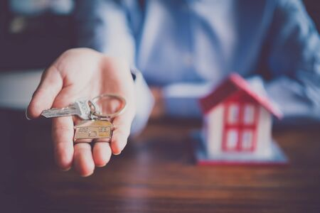 Salesperson Holding house keys concept, house keys for new house, new house purchase Banque d'images