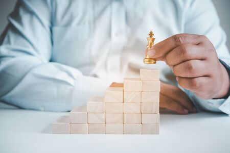 Businessman's hand picks up chess on a wooden block, concept leader  to the goal.