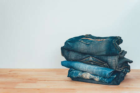 pile of jeans on a wooden background