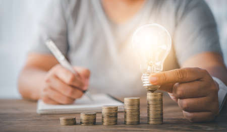 woman's hand holding a light bulb on a coin lying on a desk.Energy saving ideas to cut home expenses.