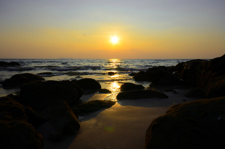 sun sets at the rocky beach photo