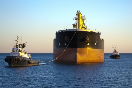 Cargo ship with two tug boats assistance arriving to the port of Alicante