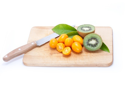fresh kumquat and kiwi on breadboard with knife Stock Photo - 9461751