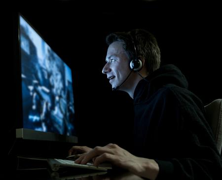 若い男が暗い部屋でコンピューター ゲームをプレイ
