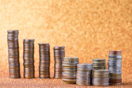 Stacks of coins on golden sparkle background. Financial concept Stock Photo