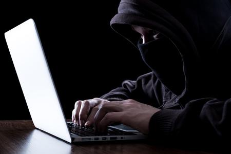 Anonieme hacker met laptop in het donker. Cybersecurityconcept