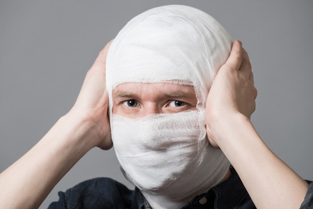 Injured young man with bandage all over his face putting hands on head. Image related with treatment of the wounds, plastic surgery, medical industry