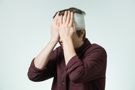 Miserable young man with bandage on his head closing face by hands. Image related with treatment of the wounds Stock fotó