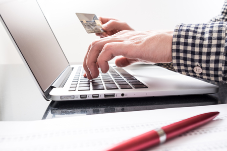 e book device: Mans hand holds credit card and another one enters data on laptop Stock Photo