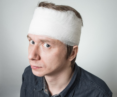 Amazed young man with bandage on his head. Image related with treatment of the wounds