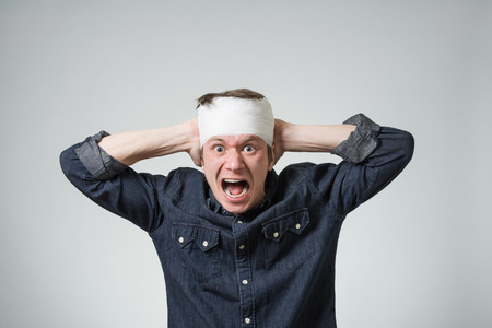 Traumatized young guy with bandage on his head putting hands on wound. Image related with treatment of the wounds Stock Photo