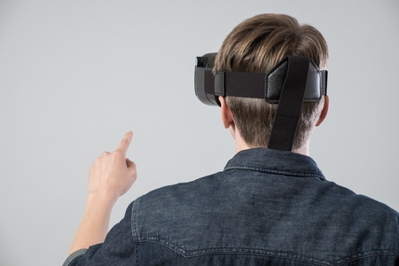 Man using virtual reality goggles and pointing on some virtual button on grey background