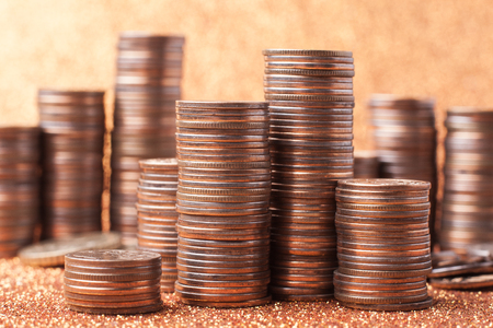 Stack of coins on golden sparkle background. Financial concept Stock Photo