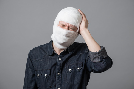Injured young man with bandage all over his face putting hand on head. Image related with treatment of the wounds, plastic surgery, medical industry Stock fotó
