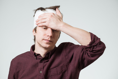 Poor young guy with bandage on his head putting hand on temple. Image related with treatment of the wounds Stock Photo
