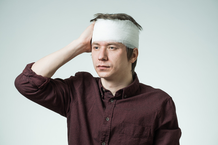 Poor young man with bandage on his head putting hand on forehead. Image related with treatment of the wounds Stock Photo