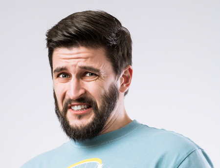 Portrait of bearded guy with disgusted expression on face Stock Photo