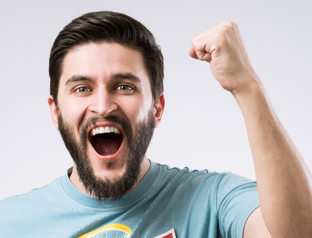 Portrait of cheerful enthusiastic bearded man with fist up as sign success