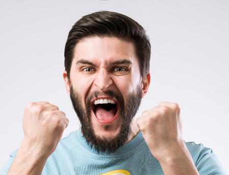 Portrait of cheerful enthusiastic bearded man with fists up as sign success