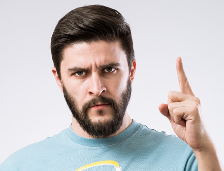 Portrait of serious bearded man with finger up as  attention sign Stock Photo
