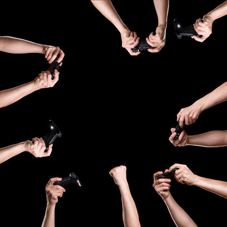 Group of hands holding joysticks on the dark background. Idea for entertainment Stock Photo