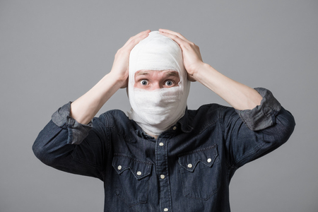 Injured young guy with bandage all over his face putting hands on head. Image related with treatment of the wounds, plastic surgery, medical industry Stock fotó