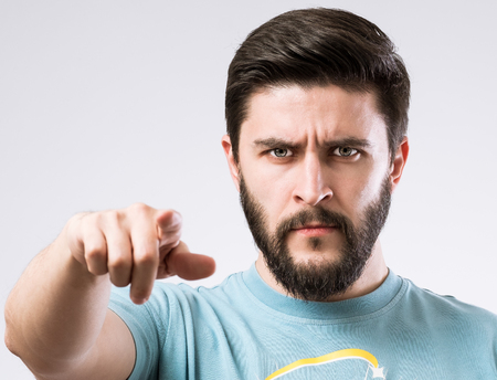 Portrait of serious bearded man pointing at you