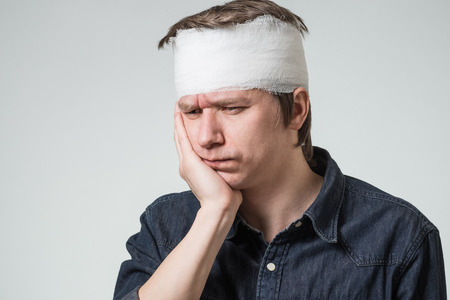 Injured young man with bandage on his head holding cheek by hand. Image related with treatment of the wounds Stock Photo