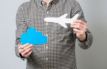 Man holding white cardboard model of airplane and blue cloud. Travel on aircraft idea