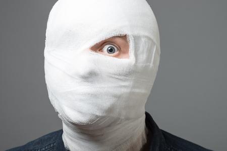 Homem jovem ferido após cirurgia com curativa em todo o rosto com um olho aberto. Imagem relacionada com o tratamento das feridas, cirurgia plástica, indústria médica