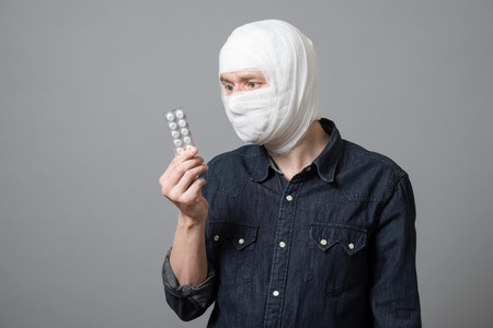 Bandaged young man holding blister pack of painkiller pills. Image related with treatment of the wounds, plastic surgery, healthcare industry Stock fotó