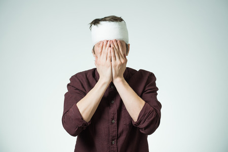 Miserable young guy with bandage on his head closing face by hands. Image related with treatment of the wounds